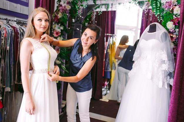 Prova femminile sul vestito da sposa in un negozio con l'assistente delle donne.