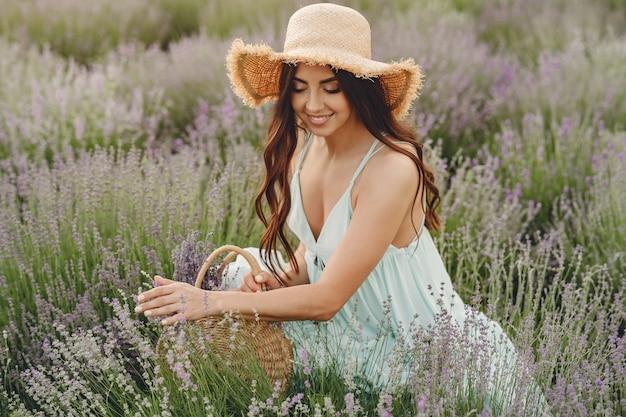 Provenza donna rilassante nel campo di lavanda. dama con un cappello di paglia. ragazza con borsa.
