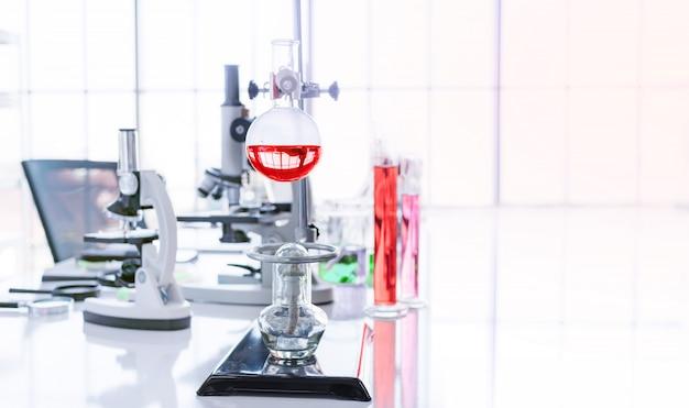 Provetta ed attrezzatura di scienza sulla tavola superiore bianca nel laboratorio di scienza