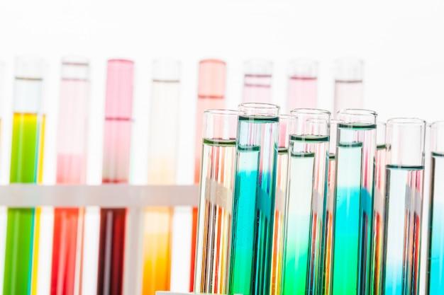 Provette chimiche di vetro del laboratorio con liquido per la fine di analisi in su