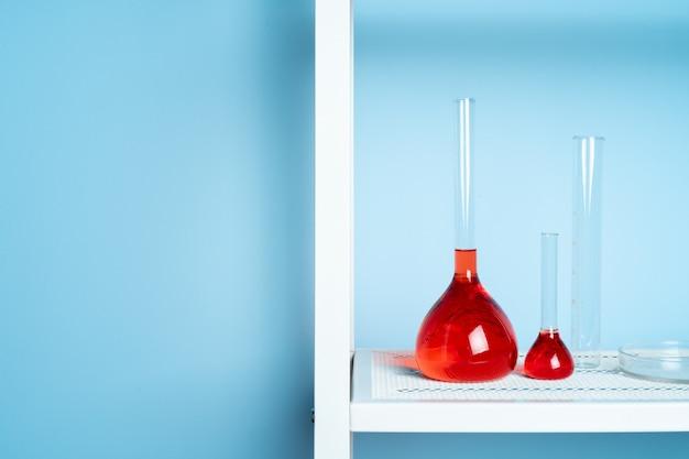 Provette con liquido rosso in laboratorio sul blu