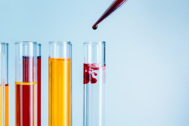 Provette di laboratorio con liquidi rossi e gialli su azzurro