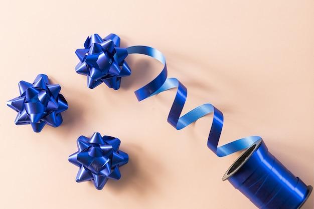 Prua per la decorazione di anniversario isolata su sfondo beige. posizione per il compleanno, la festa della mamma o il matrimonio. regalo regalo di decorazione satinata di colore lucido, design per le vacanze