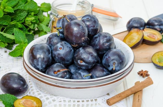 Prugna organica cruda fresca con gli ingredienti dell'ostruzione su una tavola di legno bianca.