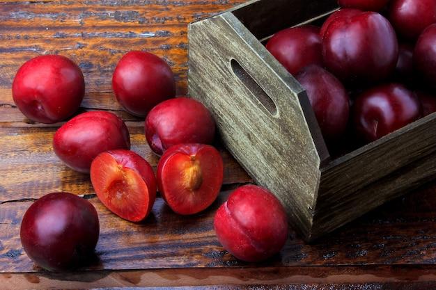 Prugne biologiche crude e fresche dentro la scatola di legno del tessuto rustico sulla tavola rustica