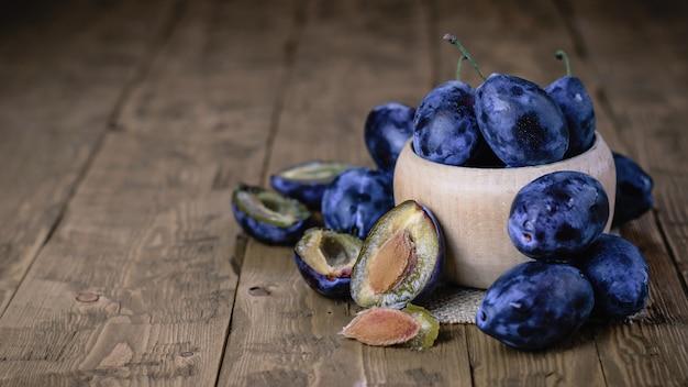 Prugne blu intere ed affettate in una ciotola su una tabella di legno.