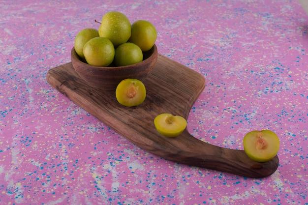 Prugne ciliegia verdi su una tavola di legno