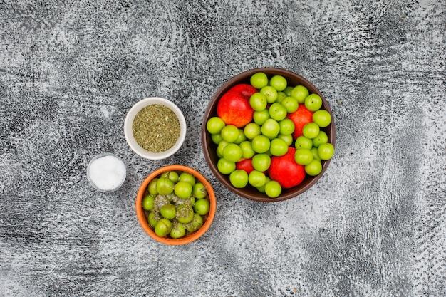 Prugne e pesche verdi in ciotole di argilla con una piccola barra di sale e vista superiore del timo secco sul lerciume grigio