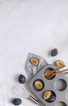 Prugne fresche, stampo in metallo per cupcake, frusta, cucchiai di legno, baccello di vaniglia