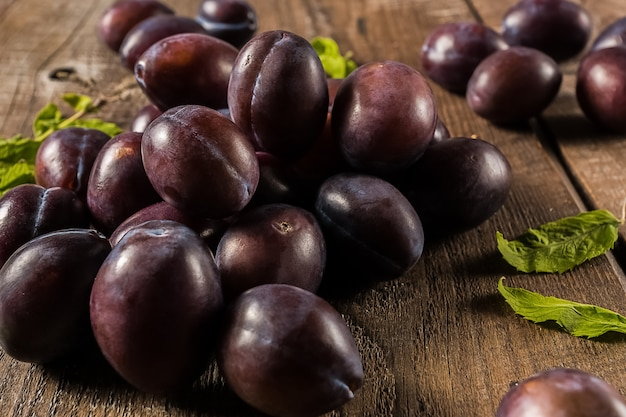 Prugne mature succose su un mucchio, sul vecchio tavolo di legno marrone.