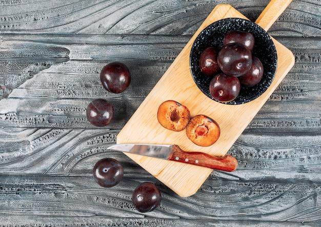Prugne molli con un coltello da frutta in un piatto e un bordo di legno su fondo di legno grigio, disposizione piana.