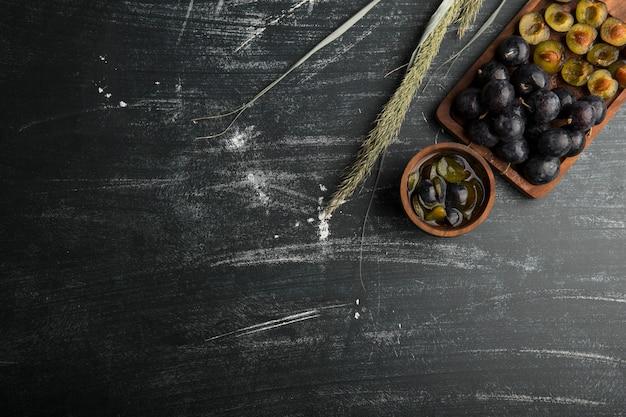 Prugne nere intere e affettate su una tavola di legno con le erbe da parte