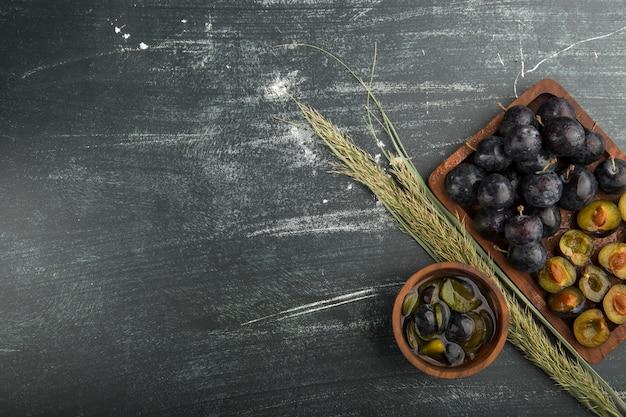 Prugne nere intere e affettate su una tavola di legno servita con erbe aromatiche
