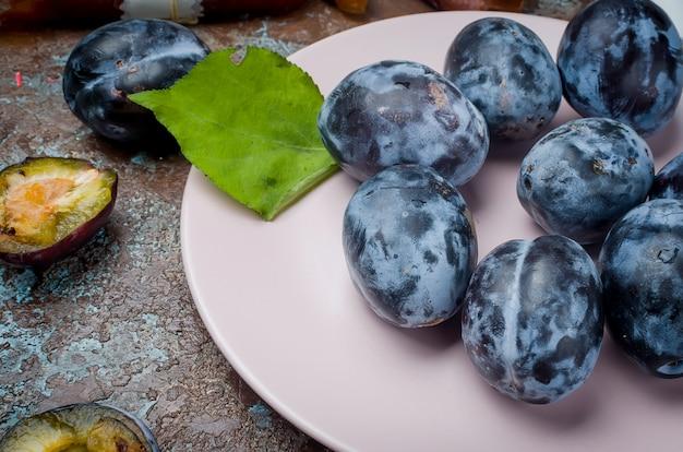 Prugne selezionate fresche in piatto ceramico su fondo scuro