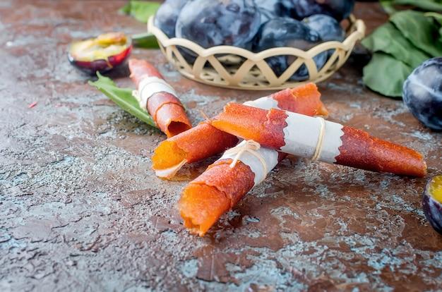 Prugne selezionate fresche sulla tavola e pastiglia di prugne su fondo scuro