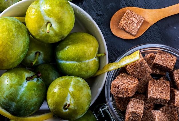 Prugne verdi fresche fresche e crude claudias. ingredienti per preparare marmellate fatte in casa a casa: prugne mature, zucchero e limone.
