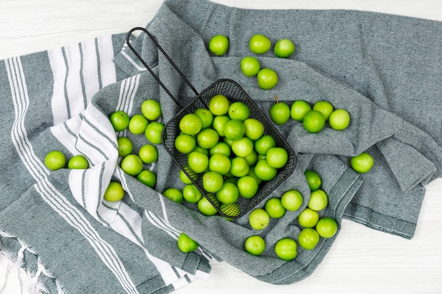 Prugne verdi sparse in un cullender nero sull'asciugamano di cucina e sul legno bianco, vista superiore.