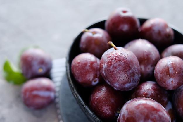 Prugne viola fresche al fondo grigio scuro della tavola