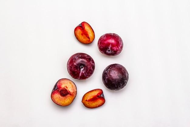 Prugne viola grandi mature. frutti interi freschi, metà affettati, semi.