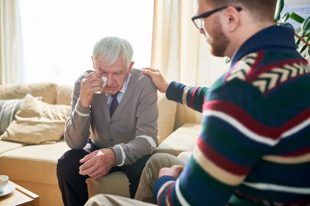 Psicologo empatico che consola un uomo anziano
