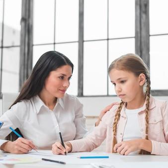 Psicologo felice che esamina la ragazza triste che disegna con il pennarello su carta da disegno