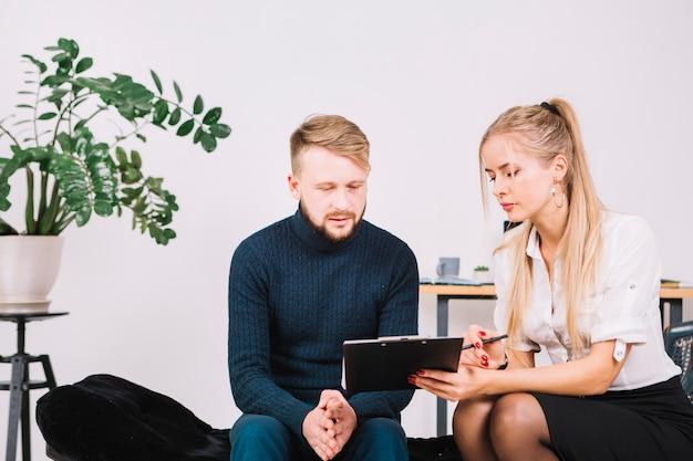 Psicologo femminile che mostra lavagna per appunti al suo paziente maschio nella clinica