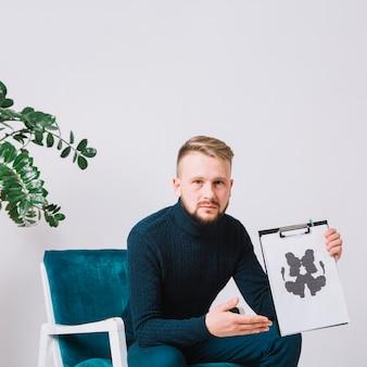 Psicologo maschio che si siede sulla sedia del braccio che mostra la carta della prova del inkblot del rorschach