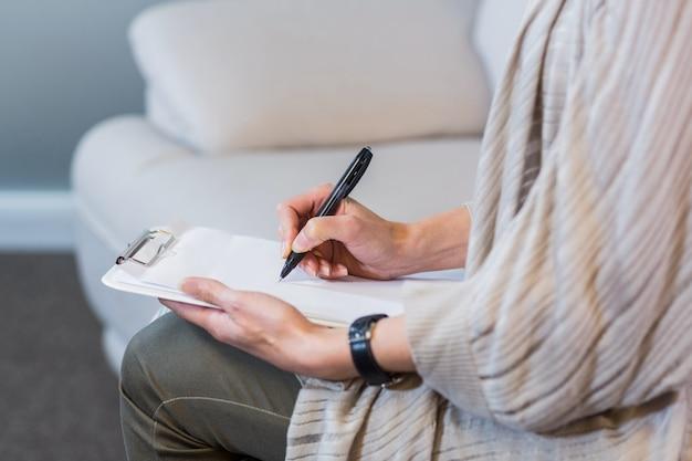 Psicologo seduto sul divano e prendere appunti