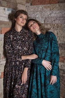 Pubblicità della moda per donna: abito, scarpe. due ragazze felici che sorridono.
