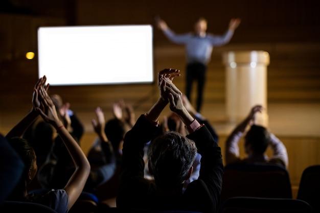 Pubblico che applaude oratore dopo la presentazione della conferenza