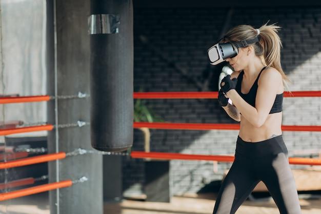 Pugilato attraente della donna nell'addestramento della cuffia avricolare di vr 360 per dare dei calci alla realtà virtuale