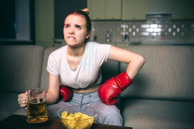 Pugilato dell'orologio della giovane donna sulla tv alla notte.