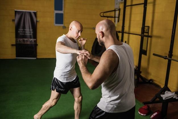 Pugilato di pratica di due pugili nello studio di forma fisica