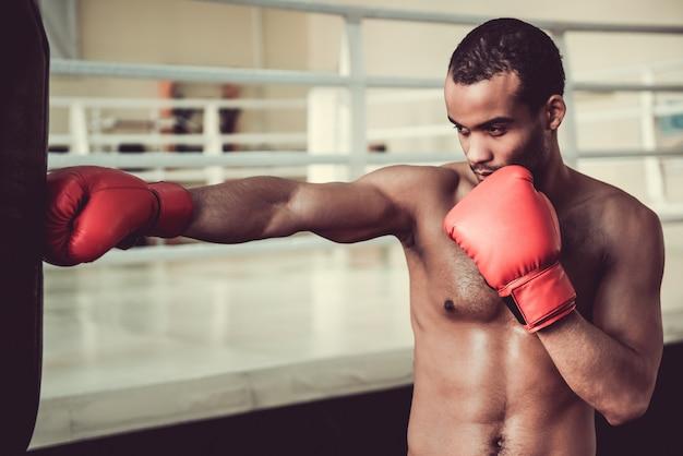 Pugile afroamericano con torso nudo in guantoni da boxe rossi.