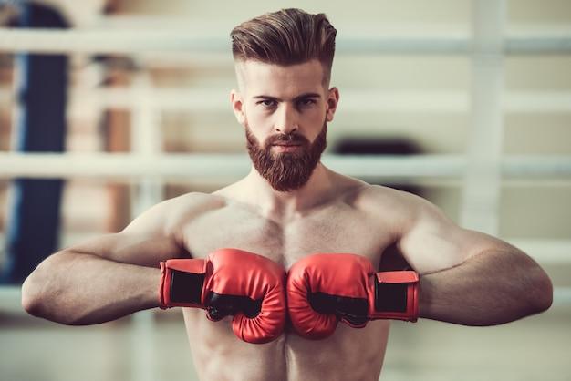 Pugile barbuto con torso nudo in guantoni da boxe rossi.