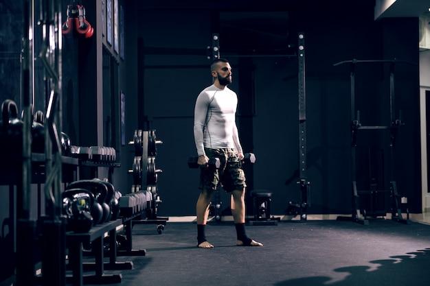Pugile potente caucasico muscolare in abiti sportivi e fasciatura sui piedi che sollevano le teste di legno in palestra.
