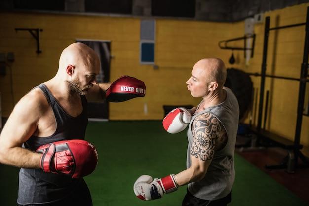 Pugili che praticano la boxe nello studio fitness