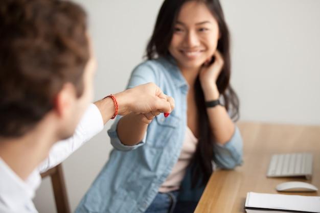 Pugno asiatico sorridente della giovane donna che urtante collega maschio sul lavoro