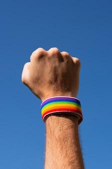 Pugno del primo piano alzato con il polsino nei colori dell'arcobaleno