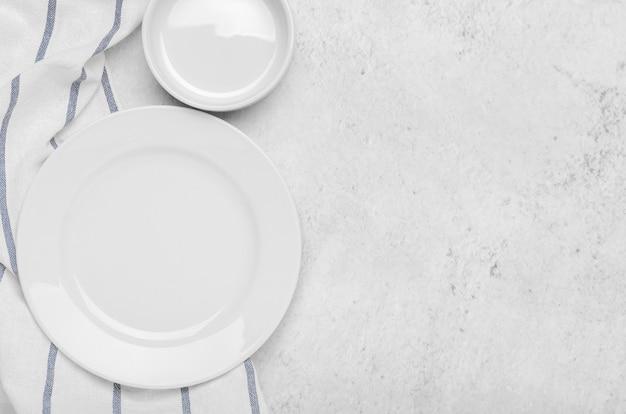 Pulire i piatti bianchi su un asciugamano fresco con strisce su una pietra leggera minimalista