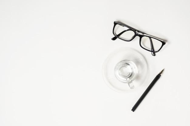 Pulire il tavolo della scrivania bianca con un bicchiere d'acqua, una penna e degli occhiali.