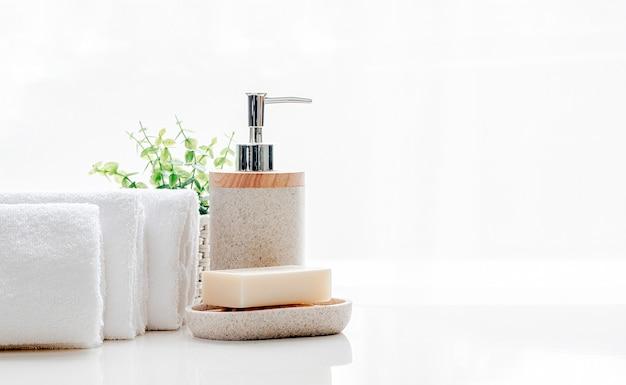 Pulisca gli asciugamani di spugna molli con sapone sulla tavola bianca, spazio della copia.