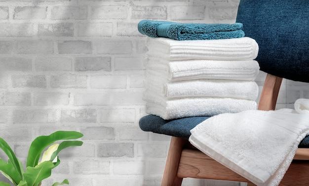 Pulisca gli asciugamani di spugna sulla sedia di legno con il fondo del muro di mattoni, copi lo spazio.