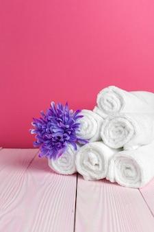 Pulisca gli asciugamani molli con il fiore sulla tavola di legno