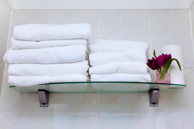 Pulisca i tulipani rosa dei fiori bianchi del bagno dello scaffale del gancio di asciugamano bianco