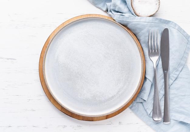 Pulisca il piatto ceramico bianco vuoto sulla tavola di pietra bianca, copi lo spazio, deridi su, vista superiore.