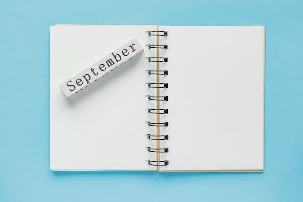 Pulisca il taccuino a spirale per le note e i messaggi e la barra del calendario di legno di settembre sull'azzurro