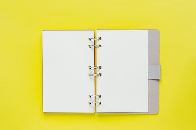 Pulisca il taccuino per gli obiettivi e le risoluzioni nel riciclaggio della copertina di carta. mockup per il tuo design. taccuino a spirale su fondo giallo.