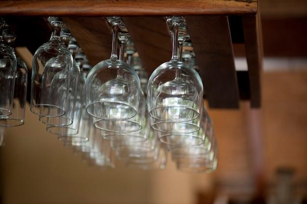 Pulisca il vetro riflettente che pende da una cremagliera del wineglass