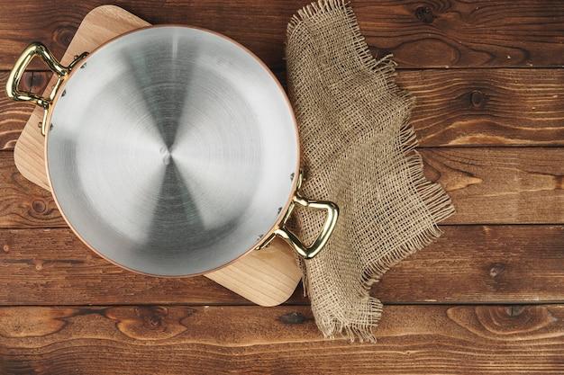Pulisca l'articolo da cucina di rame brillante sul bordo di legno